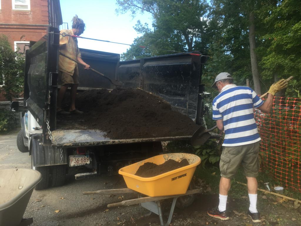 Volunteers shoveled organic compost into wheelbarrows.