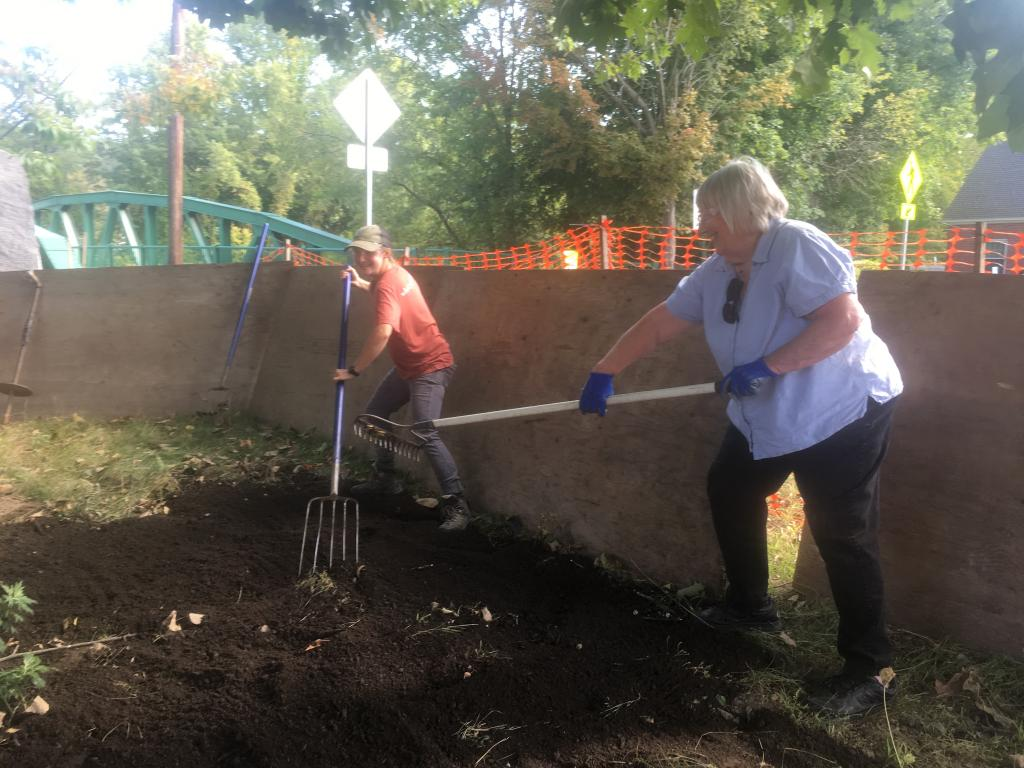 Tree committee members, Holly Hamer and Eva Ward, rake compost into place.